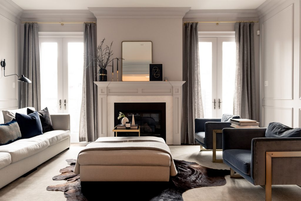 A modern living room with a beautiful custom fireplace and mantlepiece